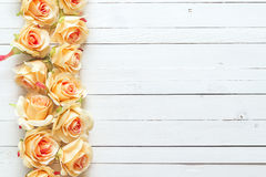Background with a border of peach roses on painted wooden planks Royalty Free Stock Photo