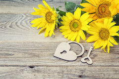 Background with bouquet of yellow sunflowers, lock-heart and key Stock Images