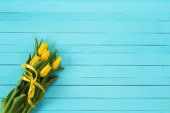 Background with bouquet of yellow tulips on blue painted wooden Stock Image