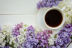 Background with branches of lilac and a Cup of black coffee. Stock Photo