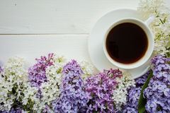 Background with branches of lilac and a Cup of black coffee. Stock Image