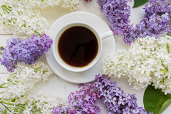 Background with branches of lilac and a Cup of black coffee. Stock Images