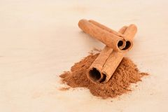 Whole cinnamon sticks and powder. Background with brown rolled cinnamon sticks and grounded culinary powder Royalty Free Stock Image