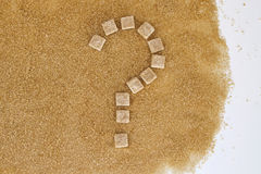 Background of brown sugar cubes shaped as a question mark. Top view. Diet unhealty sweet addiction concept Royalty Free Stock Images