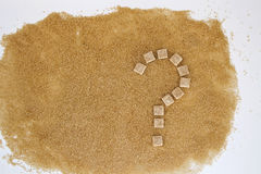 Background of brown sugar cubes shaped as a question mark. Top view. Diet unhealty sweet addiction concept Royalty Free Stock Photography
