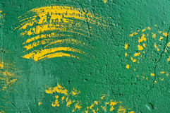 Background of brush strokes of yellow paint on a green wall Royalty Free Stock Images
