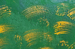 Background of brush strokes of yellow paint on a green wall Royalty Free Stock Image
