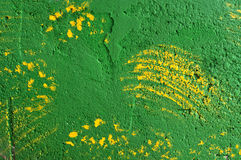Background of brush strokes of yellow paint on a green wall Stock Photography