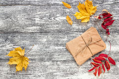 Background with a bundle of letters and autumn leaves on the gra. Y wooden boards. Space for text Stock Photos
