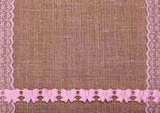 Background of burlap with pink laces Royalty Free Stock Images