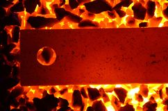 Background of burning coal anthracite and a red-hot steel strip with a hole. Stock Photography