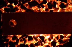 Background of burning coal anthracite and a red-hot steel strip. Royalty Free Stock Photo