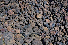 Background of burnt colored blue, violet and red stones in field of volcanic bombs. Stock Image
