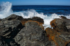 Blue waves crashing near a rocky shore Royalty Free Stock Photo