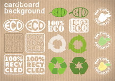 "Background cardboard with emblems «bio», ""eco"",""recycled"",""natural product"".vector illustration. The background with the real texture of cardboard Stock Photography"