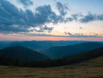 Background of Carpathians mountains, west Ukraine. The sun on horizon, dense clouds in evening sky, dark mountain range. Covered with woods. Ukrainian nature stock image