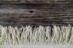 Background with carpet fringe. On the old wooden Stock Photography