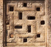 Background with carved swastika sign on Indian rock-cut architecture example. Window of 7th century Hindu temple Royalty Free Stock Photography