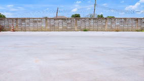 Background cement floor in car park. The bottom of the image is the copy space, The top is a wall of blogs and clouds in the blue sky. Behide of the wall royalty free stock image