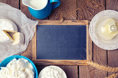 Background with chalkboard and dairy products. Focus on chalkboard. View from above Royalty Free Stock Images