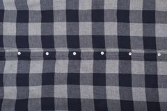 Background of checkered fabric with buttons. Close-up stock photography