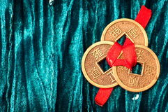 Background with Chinese lucky coins. Blue velvet background with three Chinese lucky coins tied with red ribbon royalty free stock image