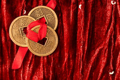 Background with Chinese lucky coins. Background with three Chinese lucky coins tied with red ribbon on red velvet fabric royalty free stock photo