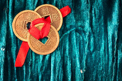 Background with Chinese lucky coins. Background with three Chinese lucky coins tied with red ribbon on turquoise velvet fabric stock image