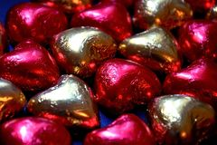 Background of chocolate candies in the form of hearts close-up. Red and gold packaging made of shiny foil. stock images