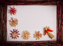 Background for Christmas greeting card- holiday straw decoration, red and claret textured paper Royalty Free Stock Images