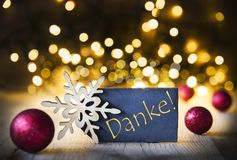 Background, Christmas Lights, Danke Means Thank You. Plate With Golden German Text Danke Means Thank You. Bright Lights In The Background. Christmas Ornament stock image