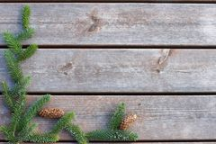 Background for Christmas and New Year from boards with spruce branch with cones.  Royalty Free Stock Photography