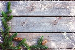 Background for Christmas and new year from boards with a spruce branch with cones and shining stars.  Royalty Free Stock Photo