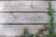 Background for Christmas and new year from boards with a spruce branch with cones and snow hops on the edge.  Stock Images