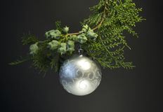 Background for Christmas and New Year. Green spruce branch with a Christmas ball on a black background. white candle with christma Royalty Free Stock Photo