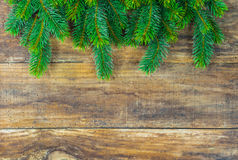 Christmas border with green fir tree branches on rustic wood background. Royalty Free Stock Photography