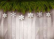 Background with Christmas tree branches. And snowflakes in front of a wooden wall. Vector stock photography