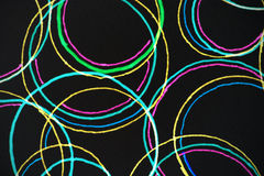 Background of circles. Abstract background composed of colorful overlapping circles, green, purple, blue and yellow drawn by felt tip pens shown against a black Royalty Free Stock Images