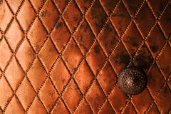 Background: close up of a copper door. Surface of an antique copper door with romb pattern and a metal knob stock photo