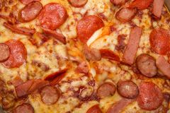 Background of close-up pizza with topping of hams, sausages and cheese Stock Photo