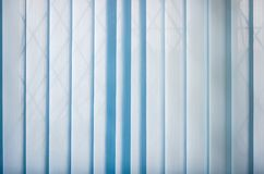 Background of the closed blue vertical blinds. Background of the blue vertical blinds made with stiffened fabric in closed position Royalty Free Stock Image