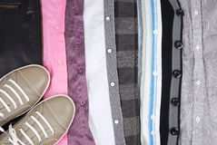 Background from clothes and a shoe. Shirts and other clothes are laid by rows Royalty Free Stock Photos