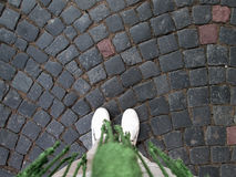 Background with cobbles. And legs of a girl in white canvas sneakers stock photography