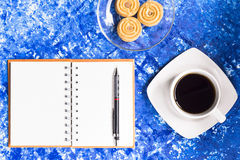 Background coffee cup and cookies  and notebook with pencil on sky table or dark tone background.Top view. Royalty Free Stock Images