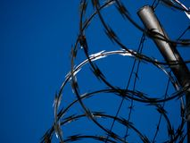 Background of a coiled barbwire fence against a blue sky forming a geometric pattern of archs horizontal. Copy space royalty free stock photography