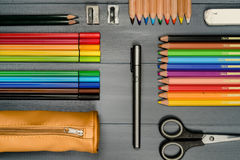 Color pencils and art supplies. A background with color pencils, markers and other art supplies on grey background Royalty Free Stock Photography