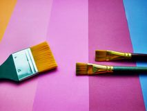 Paint brushes on a background of colored paper royalty free stock photo
