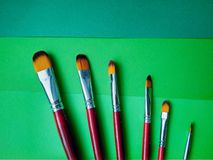 Paint brushes on a background of colored paper stock photography