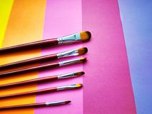 Paint brushes on a background of colored paper royalty free stock image