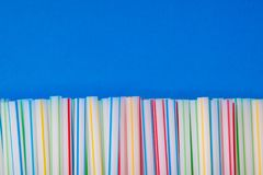 Colored tubules for drinking on a blue background royalty free stock photos